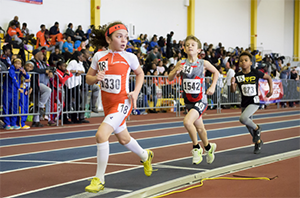 Three youth running competitively around an indoor track field