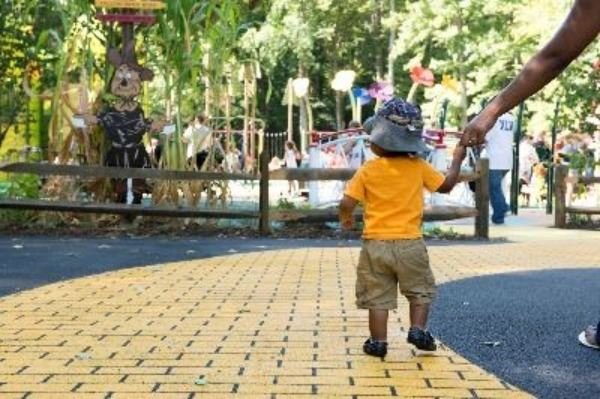 "Male toddler walking down ""yellow brick road"" in Watkins Park holding an adult's hand"