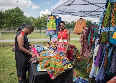 A Black couple looking at the African attire of a Juneteenth vendor at the festival
