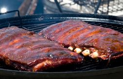 A rack of barbecue ribs cooking on a black grill.