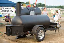 A large black barbecue apparatus with wheels attached used for smoking meats