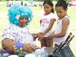 A clown wearing a bright teal wig with two girls standing close by.