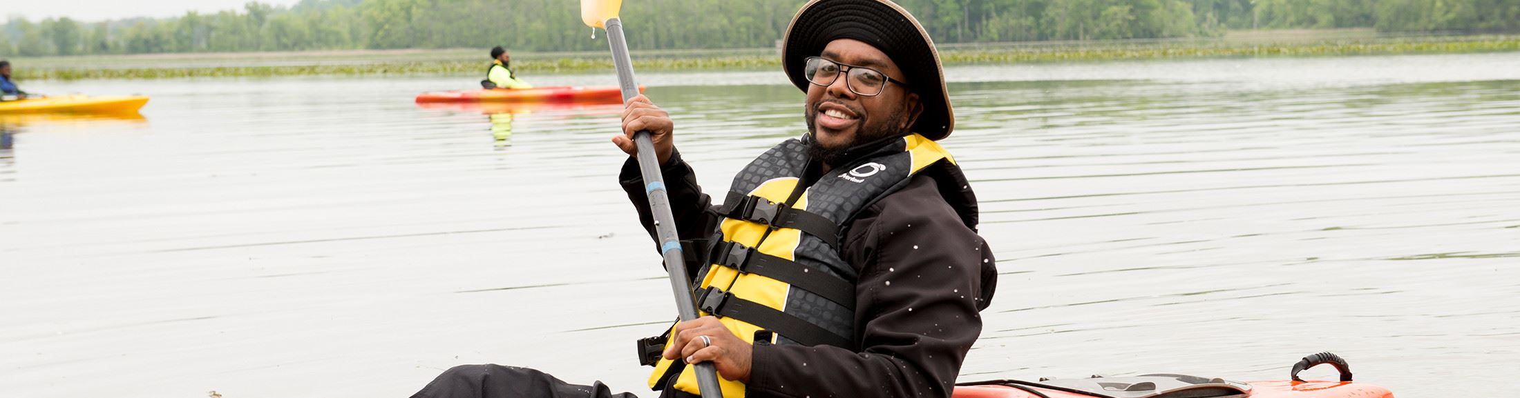 A man smiling while he kayaks