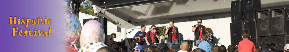 Four-man band performing on stage in front of a crowd at the Hispanic Festival