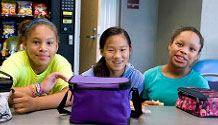three girls smiling while sitting at a table eating lunch with a vending machine behind them.