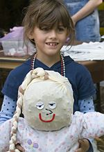 "A young girl smiling while holding a ""kindercrow"", a large handmade doll."