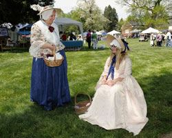 Two women dressed in blue and white dress costumes with hats and baskets.