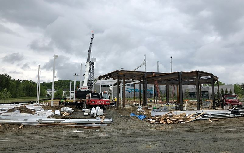 aquatic facility structure surrounded by construction vehicles and equipment such as wood, paneling,