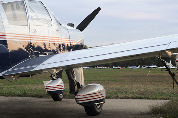 side-view of a plane with a white top, blue bottom, and thin red stripes along the side.