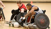 two men in wheelchairs reaching for a ball during a game of rugby