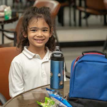 a girl sitting at the table with her lunch bag