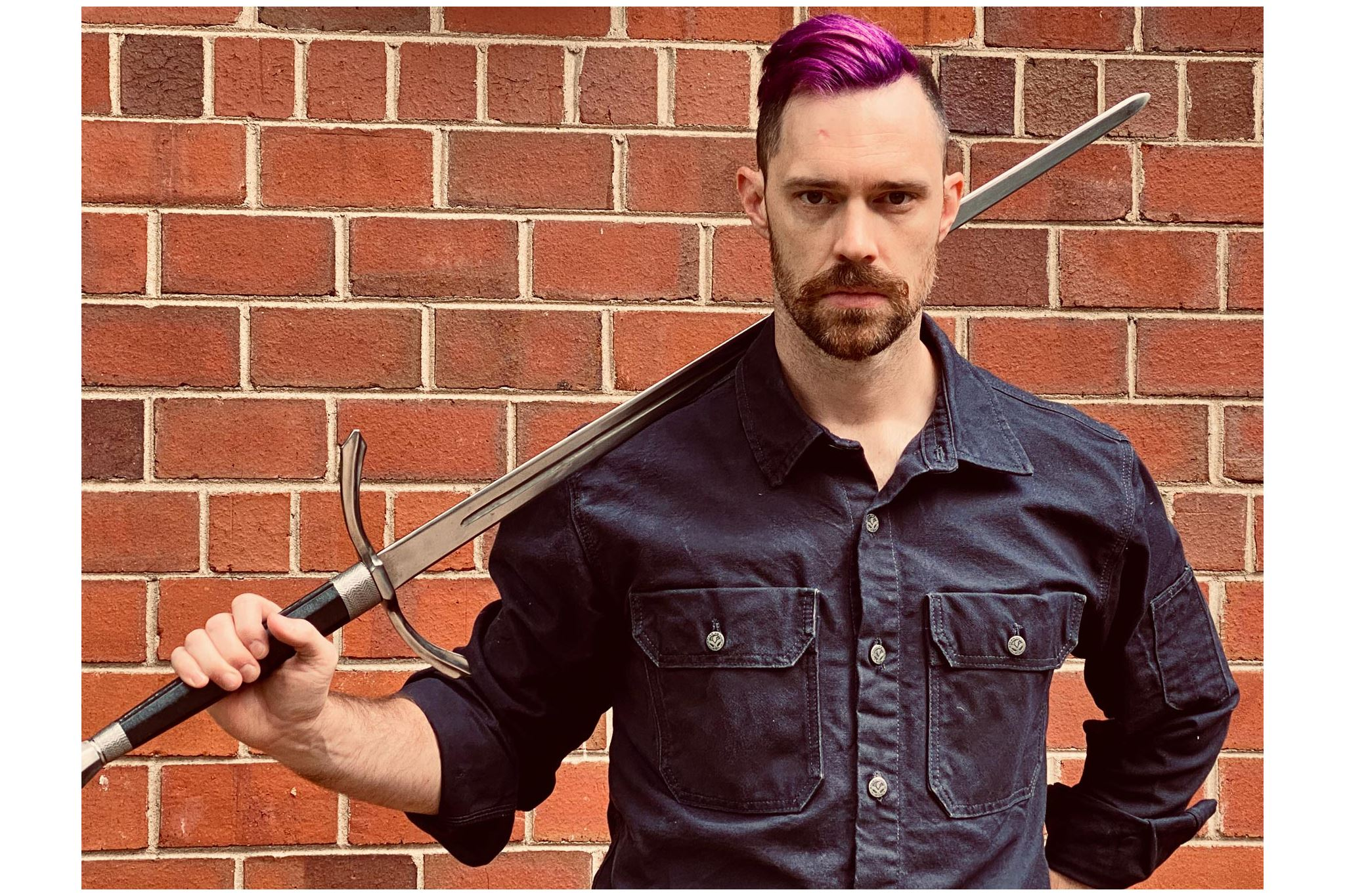 An actor with purple mohawk haircut holding a sword behind his back against a brick wall