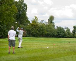 Golfers on the course taking a swing
