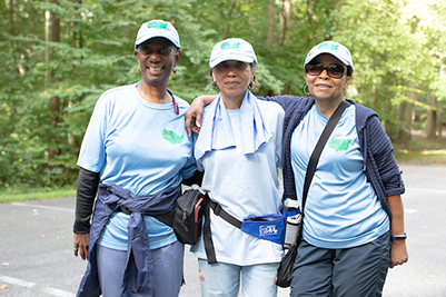 Three women in matching blue tee shirts, hats, and athletic wear smiling at the camera