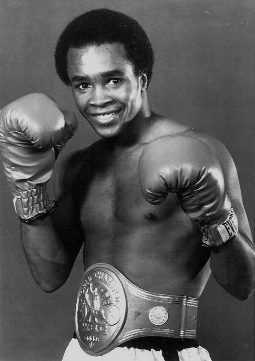 Black and white photo of Sugar Ray Leonard wearing boxing gloves and smiling
