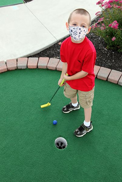 A young boy wearing a red shirt and face mask playing mini golf