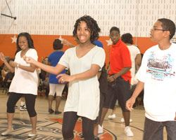 four teens dancing in the multipurpose room at good luck community center