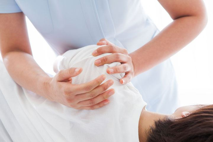 Massage therapist massaging a patron's shoulder