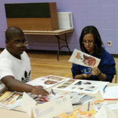 Two young people make arts and crafts using magazines and paper materials.
