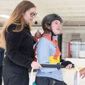 A woman teaching a girl to ice skate.