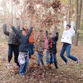 A group of kids playing in fallen leaves.