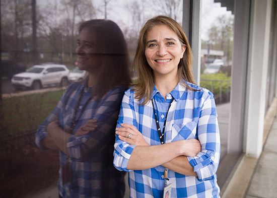 MNCPPC Staff member Annette Lehew-Cole smiling with her arms crossed wearing a blue plaid shirt.