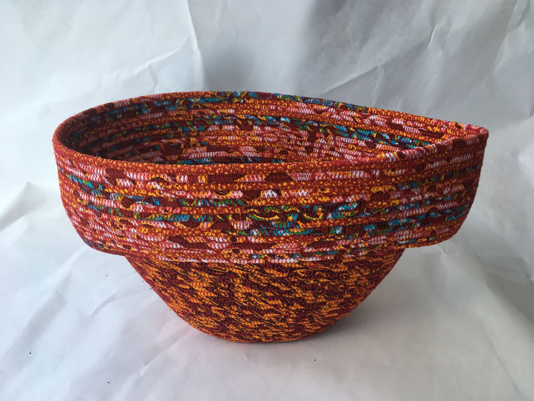 Photo of a coiled fabric, medium sized basket in red with blotches of green and blue by artists Norm