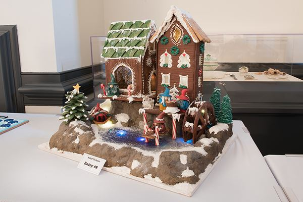 A gingerbread house decorated in icing with a family of gnomes out front