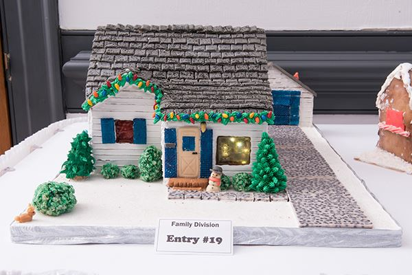 A highly detailed gingerbread house decorated with icing and candies with a snowman out front