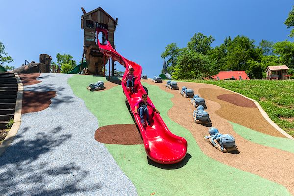 A colorful playground with a play structure with two kids sliding down the bright red slide.