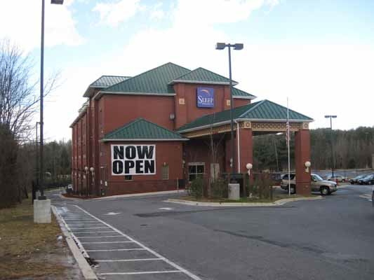 Hotel with large sign that says Now Open